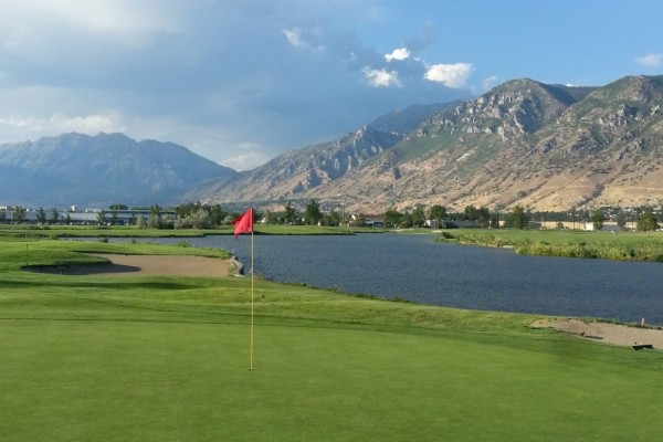 Green and Pin next to a river at the mountain's edge at East Bay Golf Course in Provo, Utah